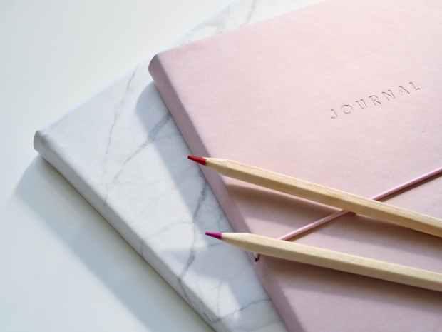 closeup photo of journal book and pencils